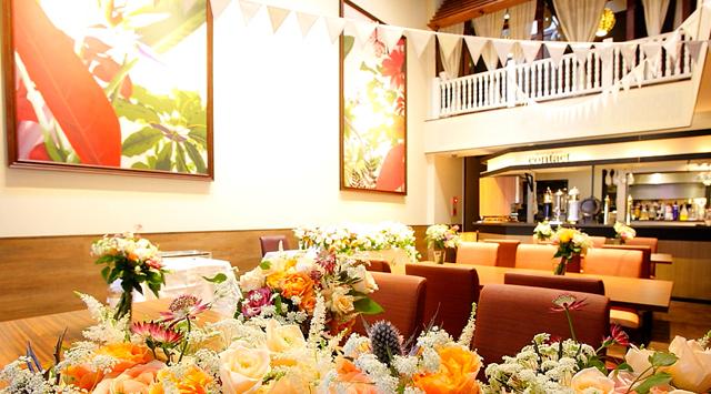 素敵な会場のご紹介をさせて頂きます。 こちらの会場は京橋にありますアロハテーブルさんです。 アロハテーブルと言えばハワイですよね。アロハテーブルはハワイのワイキキにあり日本からの観光客にも人気のレストランとして知られています。 店内はすごくおしゃれな空間でスタッフの方もみんなアロハシャツです。完全にハワイです‼サーフボードがあったりとまるでハワイにいる気分になれちゃいます。 こちらでは主に2階と使ってのパーティーが可能です。2階はテラス席があったりソファがあったりとゆったりした空間になっております。 お料理の方もハワイっぽいお料理がビュッフェ形式で楽しめます。カクテルもハワイアンカクテルをはじめとする多数のお酒が楽しめるんです。 店内は南国感でいっぱいなのでハワイやグアムなどで挙式されたりした方にかは帰国後も南国感が味わえるのでおすすめです。100インチのビックスクリーンにお二人のお写真やムービーをゲストのみなさんに見て頂きましょう。 みんなでワイワイと楽しいパーティーをご希望の新郎新婦様にはお勧めです‼ 場所はJR京橋や地下鉄四つ橋線京橋駅のすぐ近く。大変アクセスがいいのも魅力的。